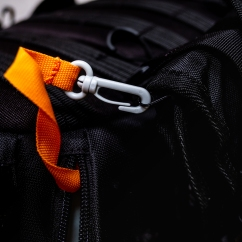 The cable organizer goes on the side of my bag and is secured by the two straps that come with the bag and also by this orange security strap. I did this for two weeks in Nepal and it didn't go anywhere.